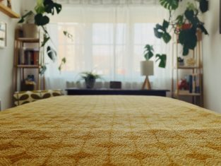 View from the bottom of a therapy couch covered in a yellow golden blanket with geometric shapes. At the end of the bed is a window covered with sheet white curtains and either side are plants on shelves.