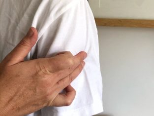 Performing a Bowen Therapy move on the upper arm
