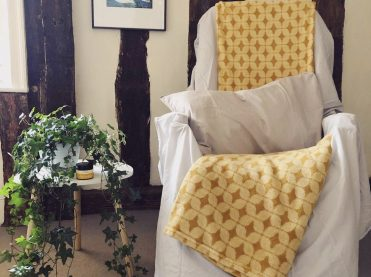 A reflexology chair ready for your treatment. There is a pillow and a soft blanket.