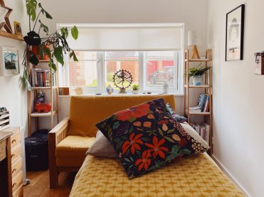 A white well lit room with a window at the end. In the foreground is a treatment couch with a yellow patterned blanket on it, a grey pillow and a navy cushion with lots of vibrant colours.