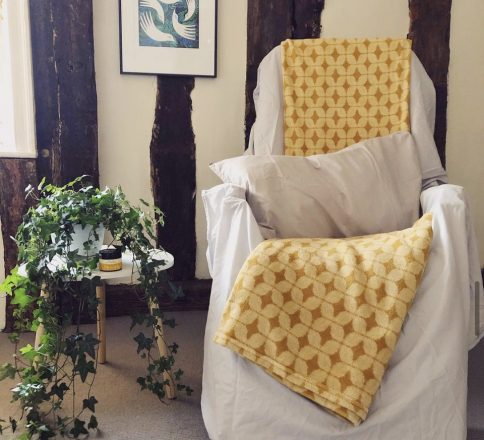A treatment chair set up for Reflexology with light grey sheets and yellow blankets. The room is timber framed and there is a picture of birds on the wall and a ivy plant on a white table to the right of the chair