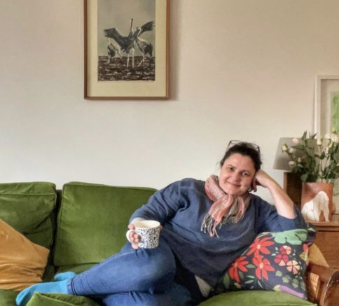 Sarah Woodhouse reclining on a green velvet sofa with a cup of tea in her hand and a bring of some birds on the wall