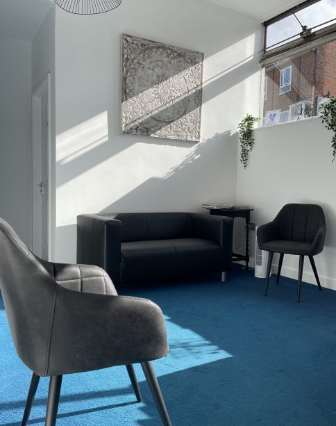 Sunlight streaming through the window into the reception of The Heart of Holistic Health in Ongar. The carpet is mid blue, the chairs and sofa are black, the walls are white.