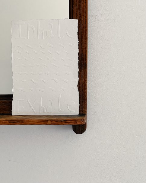 Bottom right of a mirror that has a shelf with a piece of white paper, embossed with the words 'Inhale, Exhale'