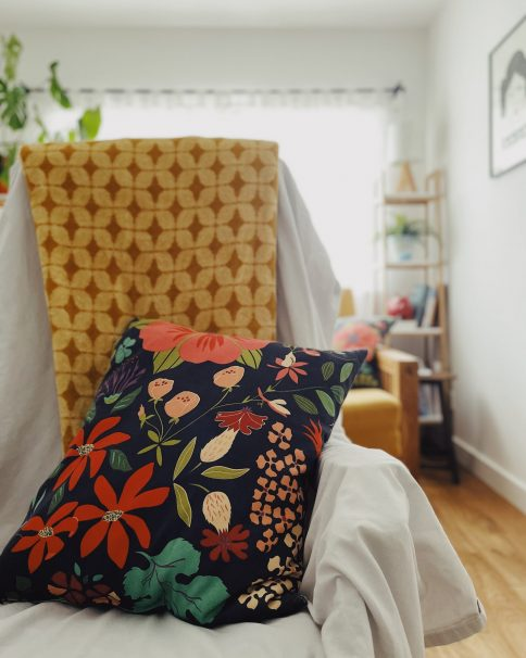 Reflexology chair with navy cushion with lots of flowers and a golden yellow blanket