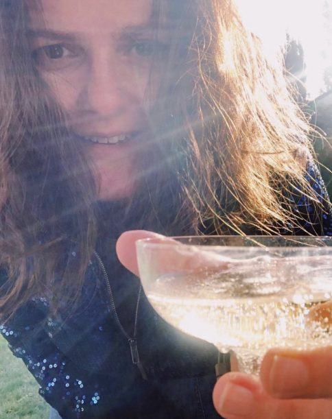 Sarah Woodhouse holding a glass of champagne in celebration