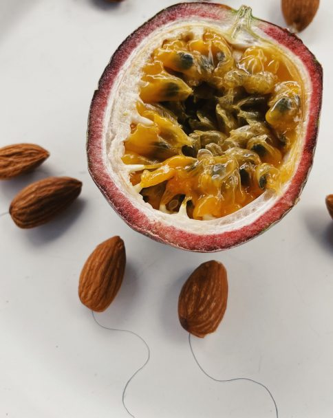 Half a passion fruit, representing an egg, scattered almonds with tails drawn in pencil representing sperm